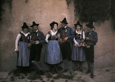 A Tyrolean singing troupe in traditional costume meets by a medieval wall, Innsbruck, Austria, 1932. By Hans Hildenbrand, autochrome.