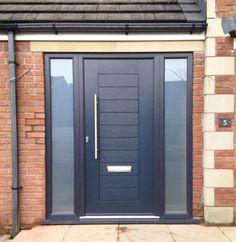 Modern front door and entrance. Door in black. Opaque glass sidelight panels on each side of the door.