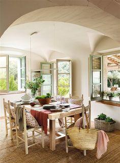 Comedor con mesa y sillas de madera bajo bóveda