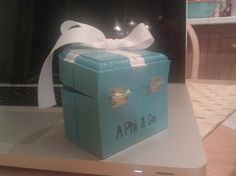 This is a pin box I made for my new little! I got a small wooden box for a dollar at the craft store, painted it blue with a white cross on top, and glued on white bow I tied. I wrote the A Phi & Co. with a sharpie and covered the whole thing with Mod Podge
