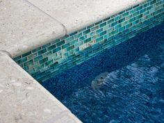Frosted-glass mosaic tile caps pool walls and echoes the design detail of front porch and interior staircase risers.