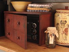 """Our Toaster Oven Cover features an apothecary style door with 4 sections and measures 20¾""""w by 11½""""h by 14""""d. Fits Toasters up to 17¼""""w by 10¼""""h by 12½""""d. Wonderfully aged Red over Black finish.    Remove Toaster Oven while in use and allow to cool completely before sliding back in. $149"""