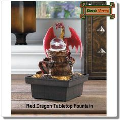 Red Dragon Tabletop Fountain - This LED light up fountain is the perfect tabletop sculpture for your castle! A regal red dragon protects his treasure while making your room glow with medieval style, and the gently cascading water and clear orb cast a soothing ambiance.