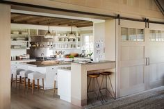 In the airy kitchen of the same home, warm white hues are paired with rustic wood grains for a look of casual cool.