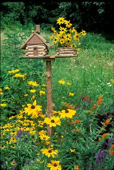 Log cabin birdhouse with attached planter filled with blackeyed susans