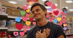 Antoni Porowski eyes closed and hands crossed over his chest with a content smile on his face and heart emoji all around him