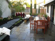 Landscape Makeovers From Turf War: Designer Ryan Crabtree delivers the goods in this space by installing a natural stone patio, a dry stream creek to assist with drainage, an outdoor dining area and privacy plants and screens to block the view of the house next door.  From DIYnetwork.com