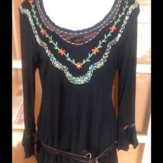 """Black  boho top with bead & ribbon So pretty and edgy at the same time. Soft thin black cotton with brown velvet ribbon trim on the yoke.  There is also turquoise and clear glass beads sewn on from shoulder to shoulder that look like a necklace. A row of embroidered orange flowers highlights the middle. The top goes to the hips with elastic  on either side. The brown velvet is again used to form a belt tied in a bow. Bell sleeves with bows, too.  Measures 18"""" chest and 28"""" long. Spectacular…"""