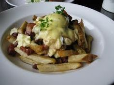 Breakfast Poutine Fries slathered in hollandaise sauce and gravy. Topped with Cheese, a poached egg and bacon.