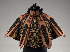 """Pingat, 1895. """"This beautifully constructed Pingat cape gains a rich and elegant appearance from its use of coordinating black beadwork embroidery on alternating flat and pleated panels of contrasting materials. That elegance can particularly be seen in the front where the embroidery on the two flannel panels line up to create a larger cohesive design oriented horizontally, as opposed to the other panels which are vertically oriented."""" (Click on pic for close up)"""