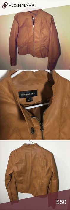 """NWOT Vegan Leather Moto Jacket Sexy moto jacket from Bagatelle in a beautiful and unique caramel color. BNWOT in stellar condition, one size too big for me. Bought for $128 from Express. Will not fit XS. Sleeves unzip for a looser fit. 100% viscose with silky lining. 22"""" long from collar, sleeves 24"""" from shoulder. Express Jackets & Coats"""