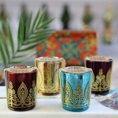 Indian Jewel Henna Glass Votives are perfect decorative items to set the right atmosphere with beautiful colors decorated with metallic gold henna print shine and shimmer. Tealight Candle Holders are colorful and make the perfect decor idea for your wedding table decorations and have a dual purpose, you can give them away to your guests as a wedding favor gift. A wonderful way to add warm light to your wedding reception table seating. Comes packaged with a gold organza ribbon and kraft tag. Wedding Giveaways For Guests, Wedding Gifts For Guests, Beach Wedding Favors, Wedding Favor Boxes, Wedding Napkins, Indian Wedding Receptions, Indian Wedding Cards, Wedding Reception Centerpieces, Indian Wedding Decorations