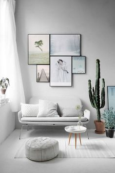 All white living room with feature picture wall, glass coffee table, sofa cacti/plants