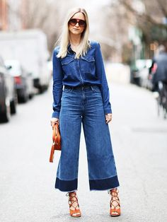 Charlotte Groeneveld of The Fashion Guitar in a denim top tucked into flared two-tone jeans and strappy heels