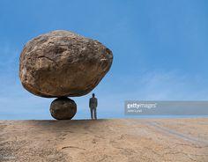 Foto de stock : Mixed race businessman under risky balancing boulder