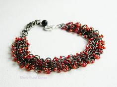 Gunmetal chainmaille bracelet with red ab seed beads
