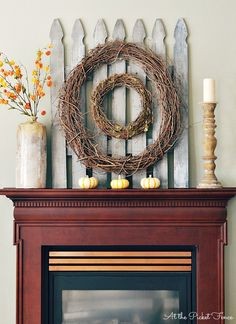 handmade picket fence fall mantel. Love the simple grapevine wreaths with the weathered wood.