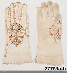 1 par fingerhandskar av vitt skinn, med stansad uddkant. På handens ovansida silkebroderier. Västbo, Småland