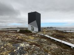"""Tower Studio / Saunders Architecture  The Tower Studio is dramatically situated on a stretch of rocky coastline in Shoal Bay, Fogo Island, Newfoundland. The studio's sculptural silhouette leans both for- ward and backward as it twists upward. For the average visitor to the island, this windowless black tower, more often than not, provokes a quizzical response and the enviable question, """"What's that?"""""""