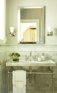 Glamorous light-filled bathroom with rich cream walls and white carrara marble subway tile backsplash and mosaic marble inset tiles on half-wall.