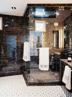 Sophistication and drama with black marble walls and a modern and graphic mosaic floor.