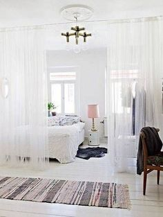 Inside this light-filled studio apartment, a sheer curtain that spans along the width of the home provides a chic alternative to bulky room dividers and allows for the entire area to reap in the benefits of all the open windows!