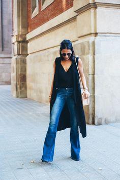 look chaleco largo sin mangas de asos color negro con jeans campana y camisola negra con accesorios dorados de maria pascual