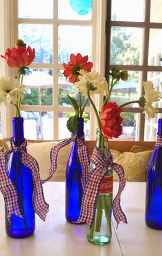 Cheerful dahlias and gerber daisies in cobalt blue wine bottles for the 4th of July..