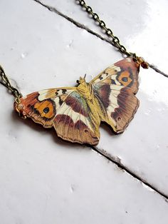 Sweet moth necklace. Adorned with Czech glass beads and hung from antique brass chain. So whimsical. Necklace measures 18 1/4 inches long with lobster clasp. Moth sits just below breastbone on average person. Moth is approx 3 x 1 1/2 inches. Made with vintage illustration applied to wood.