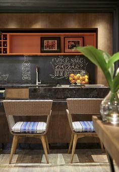 Na Decora Lider Brasília, Laísa Carpaneda e Flávia Nasr deram mais vida e cor à Varanda Gourmet  com o nicho laranja e os assentos das cadeiras em tecido listrado de azul e branco.