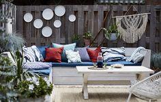Salon de jardin avec coussins et plantes suspendues.