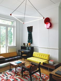 """Located just off the entry hall, this room opens onto a lush garden. The residents commissioned the overhead light from designers Sylvain Willenz and Hubert Verstraeten. """"The use of red billiard ball references Charles and Ray Eames's Hang-It-All coat rack,"""" says Smith. The wall-hung light is by the contemporary São Paulo–based designers Luciana Martins and Gerson de Oliveira. The rug is a Moroccan patchwork from the 1960s"""