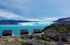 Three red huts with solar panels on the roofs, overlooking a bright aqua-coloured body of water with a white glacier in the background, under a cloudy sky.