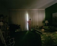 """Mom Peeking Out of Curtain, 1989 from """"Pictures from Home"""" by Larry Sultan"""