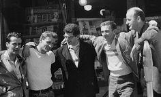 Bob Donlin, Neal Cassady, Allen Ginsberg, Robert LaVinge, and Lawrence Ferlinghetti  stand outside  City Lights Bookstore in San Francisco, California.