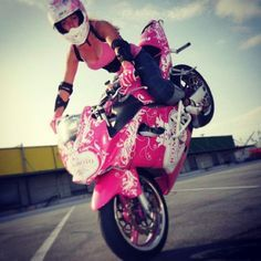 Girl in pink doing a motorcycle stunt