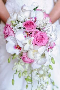 A brides teardrop shape bouquet of white dendrobium orchids, white paeony roses, white phalaeonopsis orchids and pink aqua roses.
