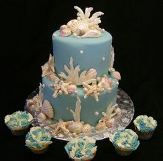 """This cake was inspired by a beach-theme. Cool blue fondant is decorated with handpainted chocolate seashells, shimmer-dusted pearls, and sugared royal icing coral. The cupcakes were done in a """"lei"""" flower-like design."""