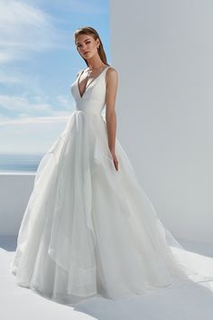 You'll be ready for the aisle in this classic deep V-neckline clean ball gown. The satin bodice with an organza ruffle skirt will light up your day. For additional support, this style is available with an illusion tulle insert added to the center front neckline or also available as a raised neckline version.