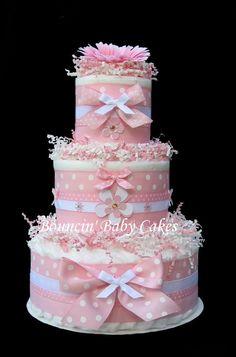 Este precioso bebé niña pañal la torta sería un centro de mesa perfecto para una es A Girl! Tema de la ducha del bebé.  Con 54 pañales Pampers arremolinaban a la perfección, capas y capas de cintas de color de rosas / blanco y mano hecho adornos de flores, este pastel de pañales es que para deleite de la mamá para ser.  Hace un adorable centro de mesa y regalos de bebé práctico!  Ingredientes: 54 pampers pañales de arrullos, tamaño 1 (8-14 lb) Capas de grosgrain de color de rosa / b...