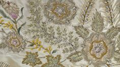 The Queen's Coronation gown emblems:  the Australian Wattle flower was done in fuzzy mimosa yellow wool & green & gold foliage;  the Fern of New Zealand was done in straight stitches using soft green silk and veined in silver & crystal; the S. African Protea was in straight stitches using soft green silk and veined in silver & crystal.