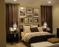 I love this elegant, romantic bedroom with the curtains to break up and soften a long wall, with photos over the bed and softened light with dark shades.