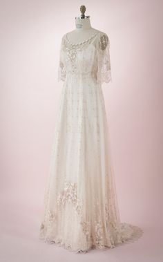 Claire by Martin McCrea   Wedding dress of delicate embroidered netting with a flower-and-vine design and embroidered appliqués over a double silk satin slip dress. Empire waist and mid-length sleeves. Optional sweeping train in the back. Available in plus size and custom sizes.