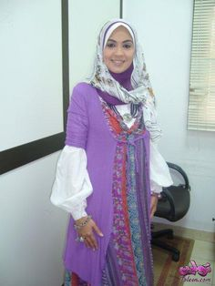 Love the look!  Doaa Amer in a purple short-sleeved jacket over a colorful French peasant print sundress with white full-sleeved shirt underneath.