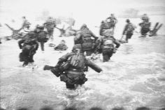 "June 6, 1944: American troops land at Omaha Beach for the invasion of Normandy known as D-Day. This photo is by Robert Capa of ""Life"" magazine. For an incredible story about how this image was taken while he dodged bullets, click through."