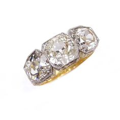 Antique three stone diamond ring, probably American c.1900, the three round brilliant cut stones to shaped box collet mounts, millegrain set, faceted gallery and tapering shoulders with engraved foliate decoration, 14ct yellow gold with platinum edge to the collets