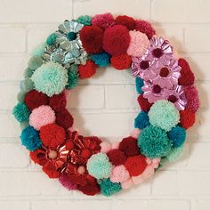 Deck your halls with vintage charm this holiday with our retro pom-pom wreath. Using ordinary crafts supplies such as pom-poms, glue, and felted balls, you can create it in a snap! To craft, hot-glue the materials on an plastic foam wreath. You can get creative with other fun embellishments, too. Try buttons, cupcake cups, pinecones, and more!