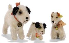 THREE STEIFF FOX TERRIERS, standing Foxy, (1314,0), white mohair, black mohair ears, patch on eye and tail base, brown and black glass eyes, black stitching, inoperative squeaker, ribbon with bell and FF button, 1930s --6½in. (16.5cm.) long (some slight thining); a small standing Foxy with chest tag and US Zone tag in seam, 1940s --3½in. (9cm.) long; and a post-war seated Foxy, (3310), script button, yellow cloth and chest tags --4in. (10cm.) high