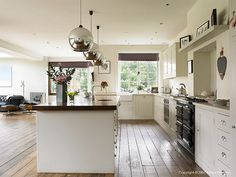 Dark floor. Off white furniture. Dark and light worktops (!), pendant nice enough, silver cup handles, units sit square to floor ie no skirting,
