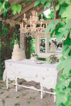 Elegant cake nook with chandelier. Event Design: Romancing the Stone Styling ---> http://www.weddingchicks.com/2014/05/08/shabby-chic-western-wedding/